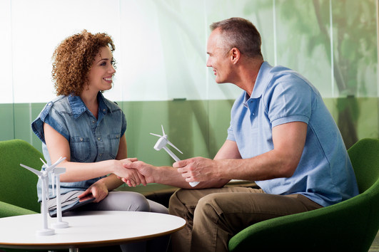 Young woman in meeting with mature man about wind turbine